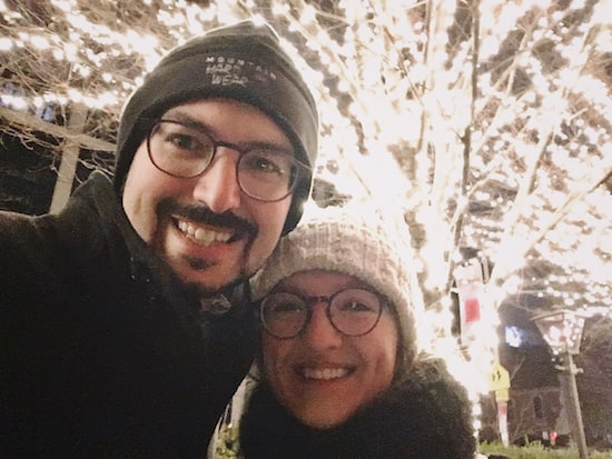 Lisa and David bundled up in front of a tree covered in lights.
