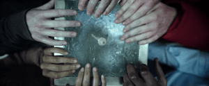 7 hands holding a block of ice with a key in it.