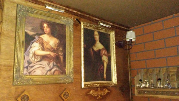 In-game: two paintings next to a shelf with bottles containing liquid.