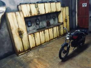 In-game: Wide angle shot of The Garage, a small motorcycle sits in the middle of the room, and a work bench and large set of cabinets sit in the background.
