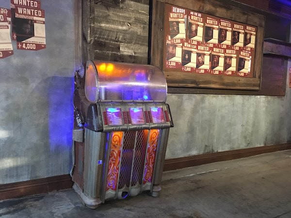 In-game: a jukebox beside a wall of wanted posters.