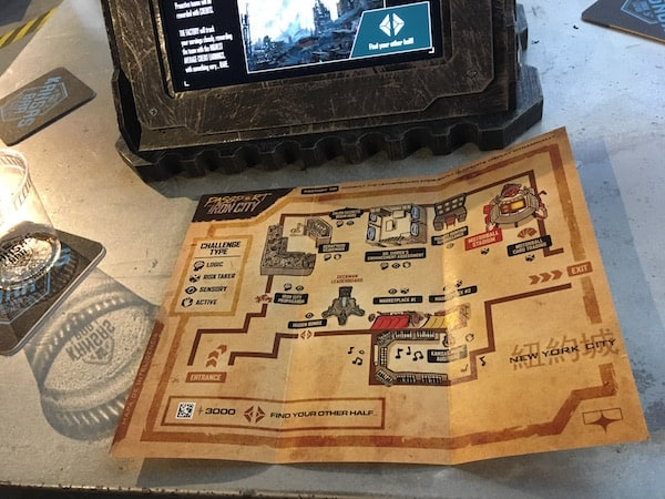 "In-game: an empty ""Kansas Bar"" glass beside a map of Iron City and an illuminated touchscreen."