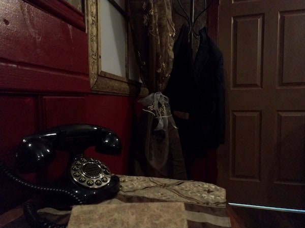 In-game: A faux rotary phone on a desk in an old study.