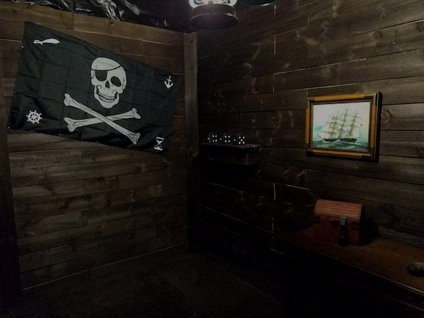 In-game:A jolly roger flag hanging on the wall of a pirate ship.