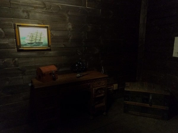 In-game: The captain's desk and a locked chest aboard a pirate ship.