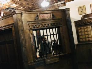 In-game: A cashier standing behind a barred window in an elegant wooden bank.