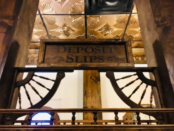 "In-game: A sign that reads, ""Deposit Slips"" surrounded by intricate woodwork, above it is a beautiful gold ceiling."