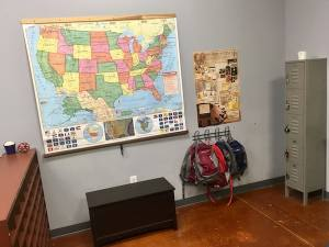 In-game: Lockers, bag hangers, and a map of the USA in a classroom.