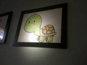 In-game: An image of a cartoon turtle hanging on the wall of a dark room.
