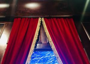 In-game: Red and gold curtains covering the wood walls and a window with a snow storm.