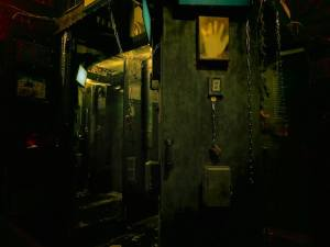In-gameA wall with chains a digital display and a handprint in a gritty murder basement.