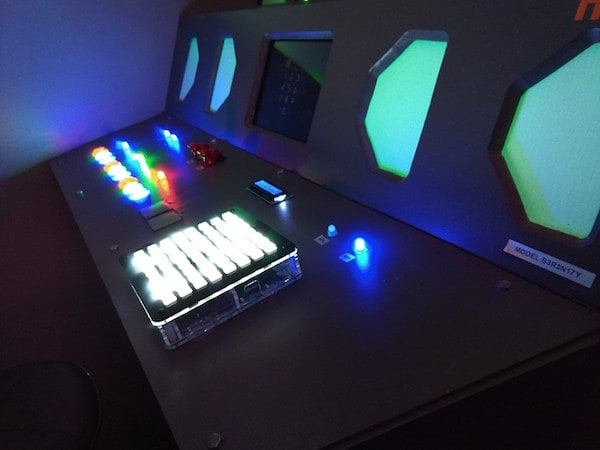 In-game: A space ship control panel with multi-colored glowing buttons.