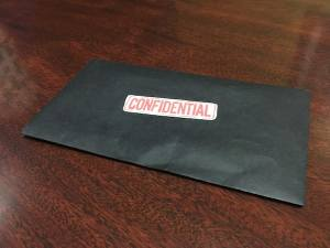 "In-game: closeup of a black envelope labeled ""Confidential"" in red ink."