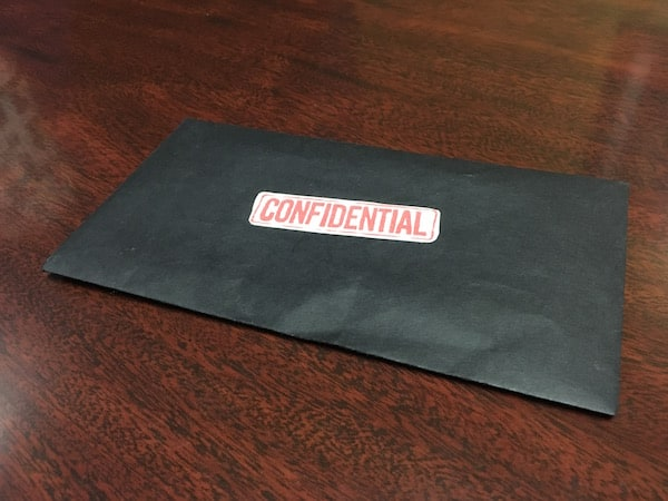 """In-game: closeup of a black envelope labeled """"Confidential"""" in red ink."""