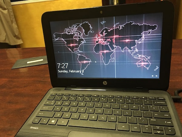 In-game: A computer with a world map on the lockscreen in an office.