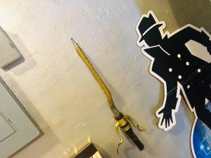 In-game: A wizard's broom and a cardboard cutout of a black and white cartoony detective.