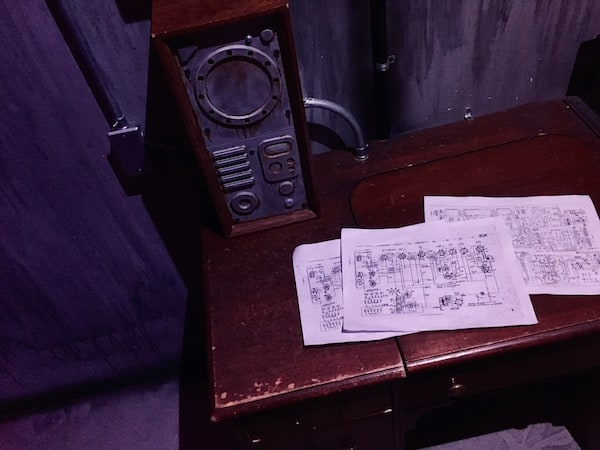 In-game: closeup of a desk with strange schematics beside a large piece of equipment