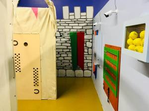 In-game: A shot of Attack The Castle's set, a painted castle wall behind a tent.