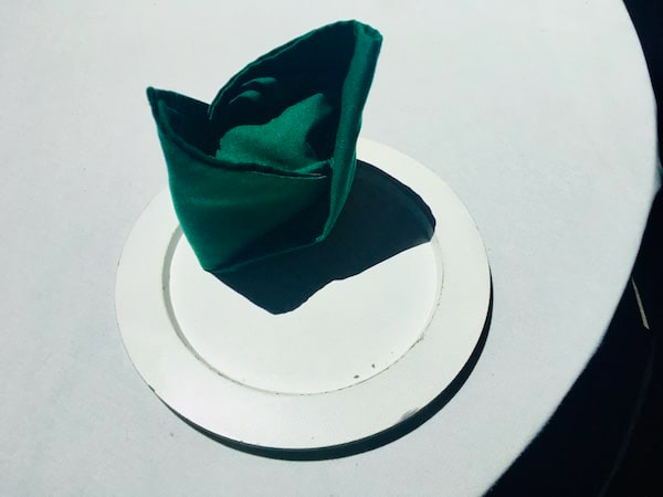 In-game: A neatly folded green napkin on a white plate and white tablecloth.