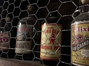 """In-game: closeup of some liquor bottles. one reads, """"Red's Pure Old Panther Piss."""""""