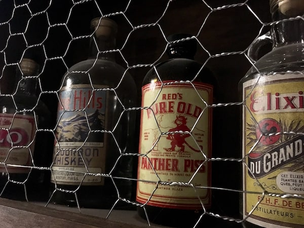 "In-game: closeup of some liquor bottles. one reads, ""Red's Pure Old Panther Piss."""