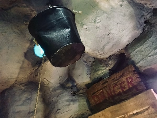 """In-game: A bucket hanging from a rope in a mine. There is a wooden sign labeled """"DANGER"""" hanging from the wall."""