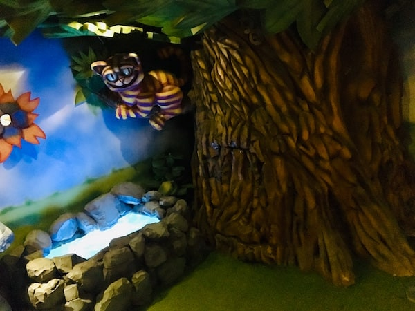 In-game: The Cheshire Cat hanging in a big tree branch over a pool of water.