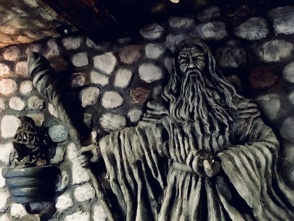 In-game: A statue of a wizard holding a crystal ball carved into a stone wall.