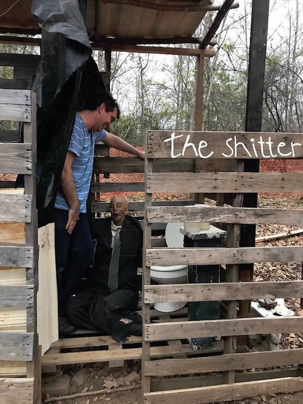 "Dan Egnor standing in an outhouse labeled ""The Shitter"" looking into the toilet."