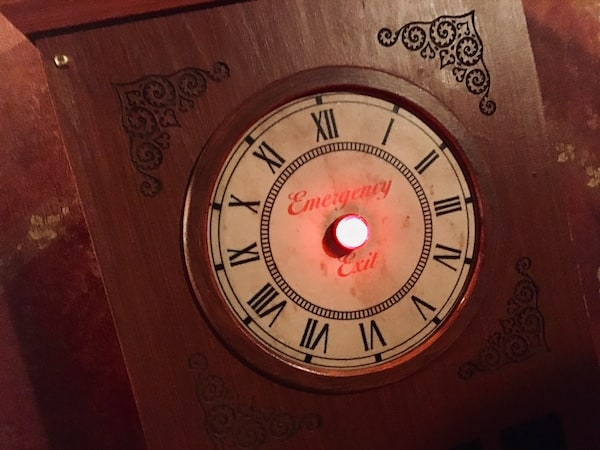 In-game: Closeup of a glowing red Emergency Exit button.