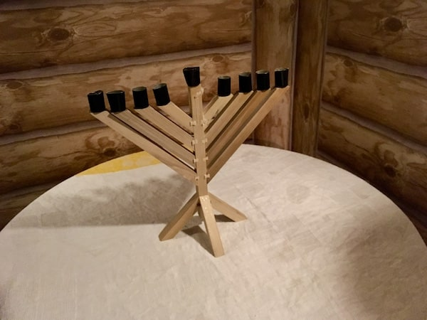 In-game: A wooden menorah on a table in a cabin.