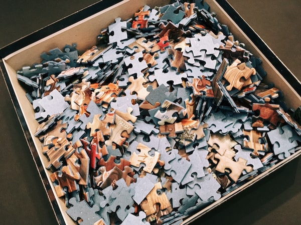 An opened jigsaw puzzle box filled with pieces.