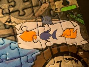 Closeup of a puzzle element depicting three different types of fish.