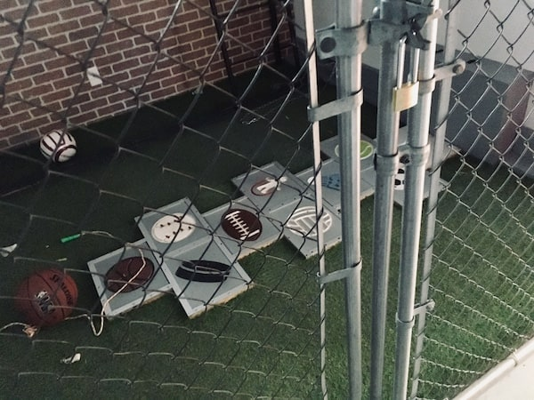 In-game: A hopscotch with each tile bearing a piece of sporting equipment shot through the gate of a schoolyard.
