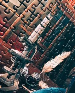 Portion of an assembled jigsaw puzzle featuring a microscope and a quill pen.