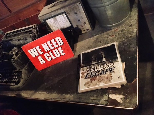 "In-game: A red we need a clue sign sitting beside a laminated and spiral-bound book labeled ""CELLAR ESCAPE."" All surrounded by a beautiful set."