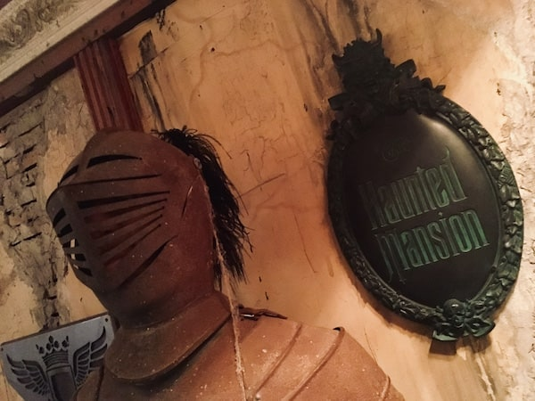 """In-game: a suit of armor in front of worn plaster walls, the insignia for Disney's """"Haunted Mansion"""" hands proudly."""