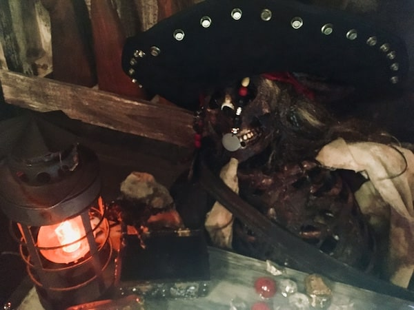 In-game: a dead and decaying pirate captain surrounded by treasure.