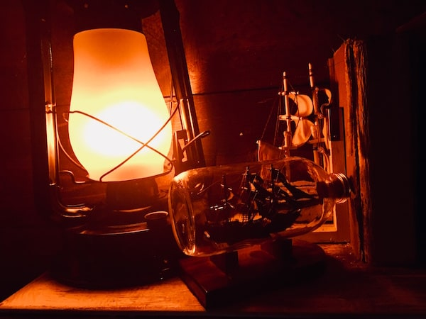 In-game: Closeup of a shelf with a lantern and a ship in a bottle.