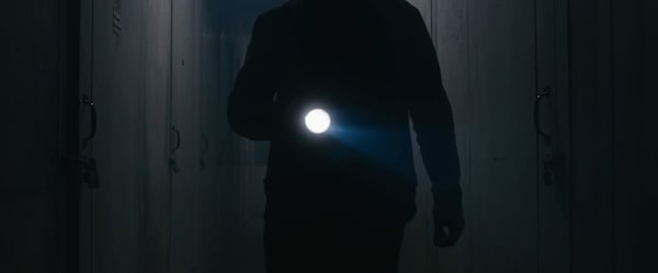Closeup of a man with a flashlight searching a hallway of storage units.
