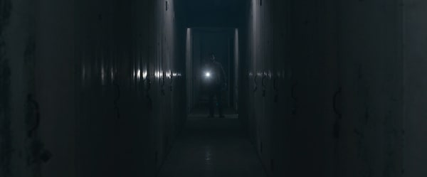 A man with a flashlight off in the distance down a long hall of storage units.