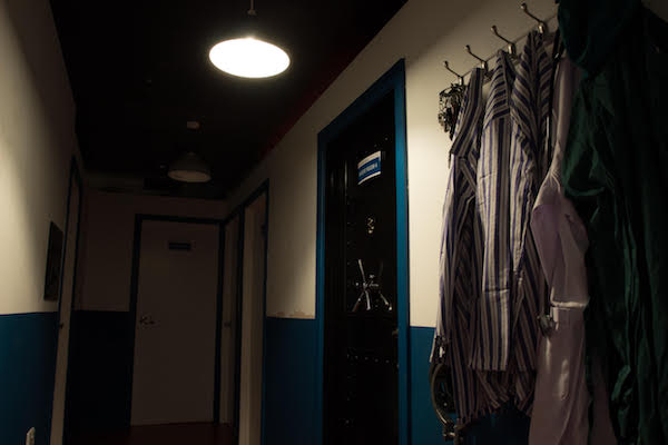 In-game: The hallway of an asylum with patient clothes hanging from hooks on the wall.