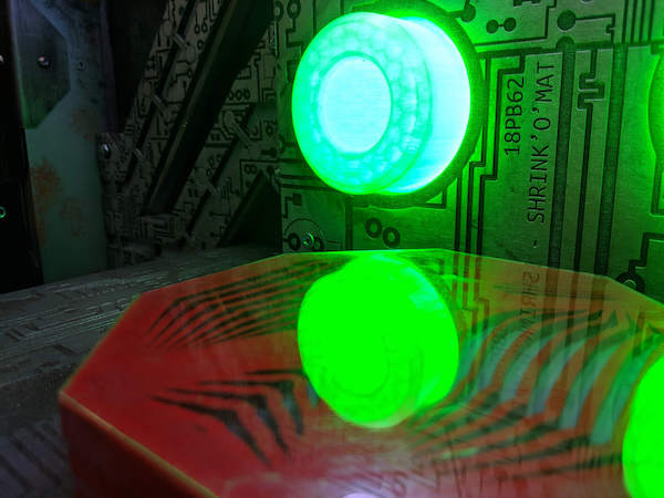 In-game: Closeup of a circuit board with a large glowing green LED.
