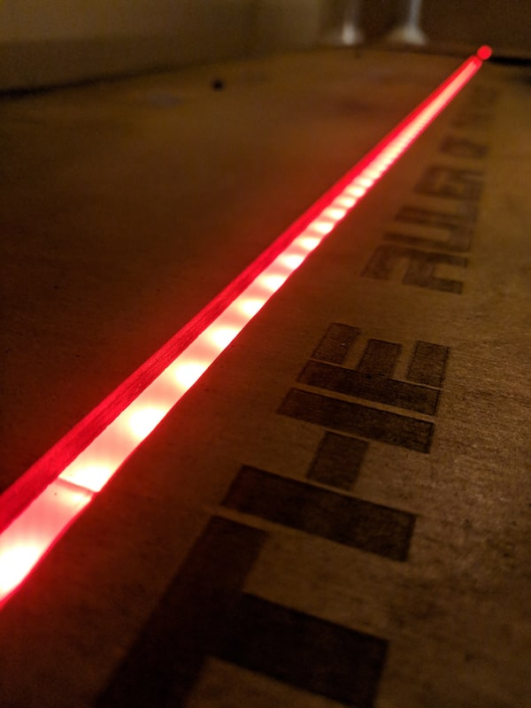 "In-game: a red glowing LED strip labeled ""THE RULER OF..."""