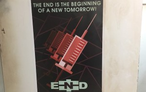 """In-game: A poster of needles labeled, """"The end is the beginning of a new tomorrow!"""""""