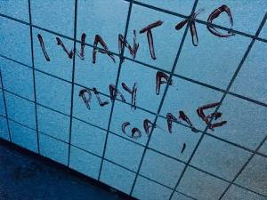 """In-game: """"I want to play a game"""" painted in blood on a white tiled wall."""