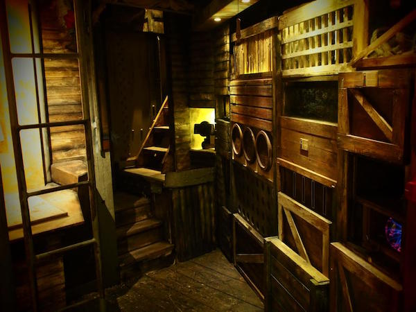 In-game: A wooden ship's comaptment with unusual crates and storage containers built into the walls.