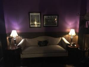 In-game: A purple walled study with a couch flanked by table lamps.