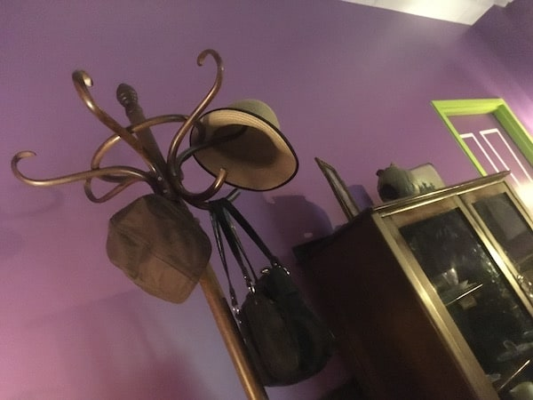In-game: a coat rack with a pair of hats and a handbag hanging from it.
