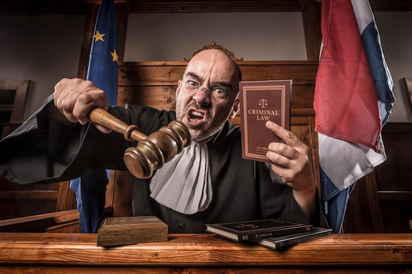 An enraged judge staring into directly into the camera, pointing with a gavel and holding up a book of Criminal Law.